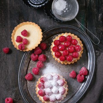 Unfinished and ready to eat tartlets with custard, sugar powder and fresh raspberries, served on vintage metal tray with baking forms and sieve over old wooden table. Dark rustic style. Flat lay