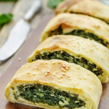 strudel with spinach and ricotta on a dark wood background. the toning. selective focus
