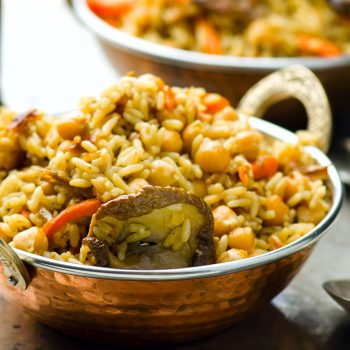 vegetarian pilaf with chick-pea and mushrooms in a copper Indian bowl. selective focus