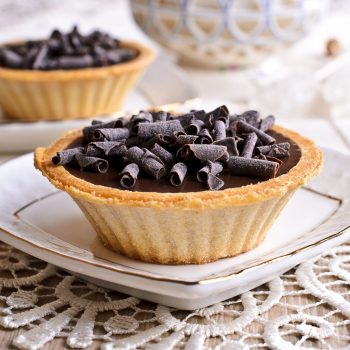 Tartlet with dark chocolate on a white saucer