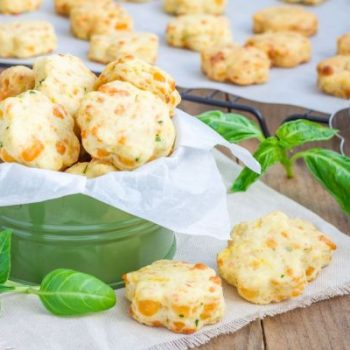 47675566 - fresh baked cheese cookies with basil, closeup