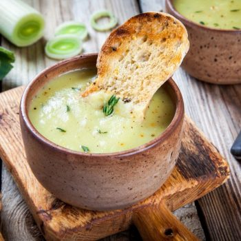 homemade cream of leek soup with croutons on wooden table