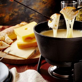 62635343 - gourmet swiss fondue dinner on a winter evening with assorted cheeses on a board alongside a heated pot of cheese fondue with two forks dipping bread and white wine behind in a tavern or restaurant