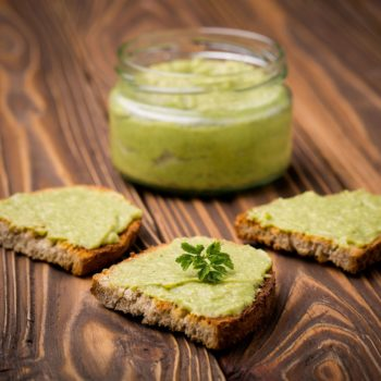 48436318 - natural homemade diy vegan very healthy green paste made of avocado, millet gruel, chilli, garlic and parsley on bread and wooden table