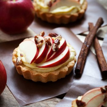 Tartlets with apple slices, cream and pecan filling